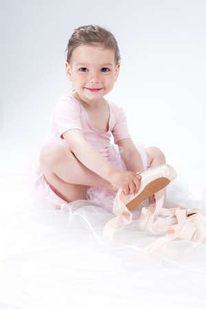 toes: Natural Portrait of Cute Little Ballerina Putting on Mini Toes. Against White Background.Vertical Image Stock Photo