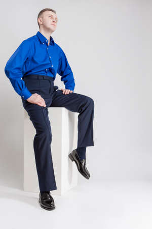 against white: Caucasian Man Sitting on White Box and Looking Upwards. Posing Against White. Vertical Image Orientation