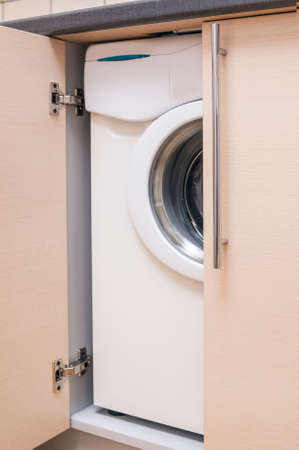 cabinetry: Kitchen Mini Cabinet with Portrable Washing Machine Inside. Vertical Image Composition
