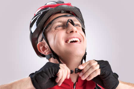 cycler: Safety Concept and Ideas. Male Caucasian Cyclist Checking Road Helmet. Wearing Glasses. Against White Background. Horizontal Image Stock Photo