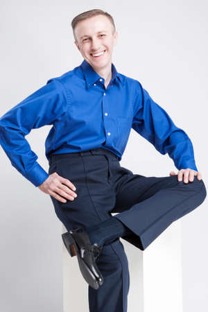against white: Happy Smiling Caucasian Man Sitting on White Box and Laughing. Posing Against White. Vertical Image Orientation