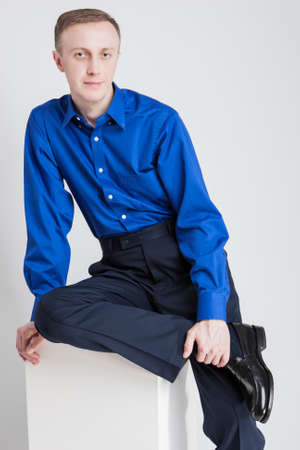 against white: Portrait of Handsome Caucasian Man Posing in Blue Shirt and Dark Blue Trousers Against White. Vertical Image Orientation