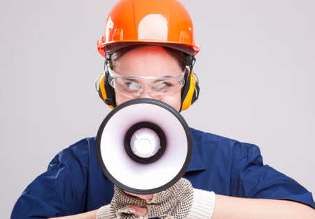 boiler suit: Professions Concepts and Ideas.Portrait of Expressive Caucasian Female With Loudspeaker Horn Shouting In Hardhat. Equipped with  Coverall. Horizontal Shot
