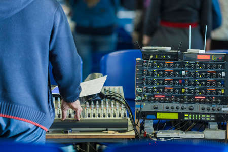 decibels: Sound Operator at Work in front of Sound Mixing Console. Horizontal Image Composition