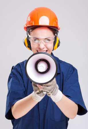 boiler suit: Shouting Caucasian Female Worker Posing with Megaphone and Wearing Hardhat for Protection. Vertical Image Composition