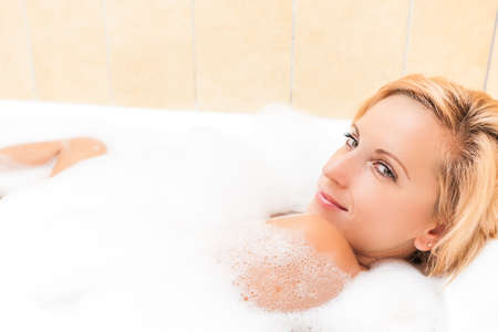 relaxion: Portrait of Sexy Caucasian Blond Female Relaxing in Foamy Bathtub.Horizontal Image Composition Stock Photo