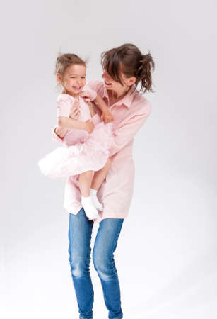 Family Concepts And Ideas. Mother and Daughter Embracing and Hugging Together. Against White Background. Vertical Shot