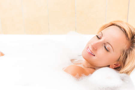 relaxion: Portrait of Sexy Caucasian Blond Female Relaxing in Foamy Bathtub.Horizontal Image Stock Photo