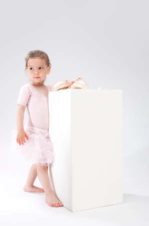 pointes: Children Concepts and Ideas. Little Cute Caucasian Girl Poses With Miniature Pointes. Against White. Vertical Image Orientation Stock Photo