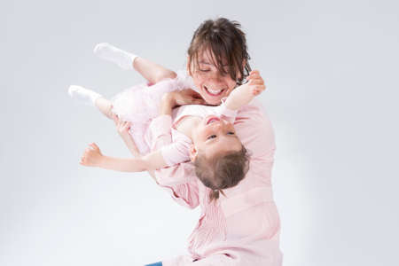 Portrait of Young Caucasian Female and Her Little Daughter Playing and Embracing Together. Against White. Horizontal Image Stock Photo