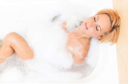 blondy: Spa and Welness Concepts and Ideas. Sensual Caucasian Blond Woman Relaxing In Bathtub with Bubble Foam.Horizontal Image Composition Stock Photo