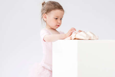 pointes: Children Concepts and Ideas. Little Cute Caucasian Girl Poses With Miniature Pointes. Against White. Horizontal Image Orientation Stock Photo