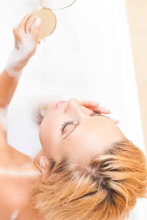 vertical wellness: Spa and Wellness Concepts and Ideas. Caucasian Blond Woman During Skin Makeup Process in Bathtub. Vertical Image