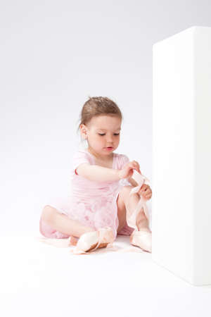 pointes: Portrait of Cute Concentrated Caucasian Girl Trying On Miniature Pointes. Sitting on Floor. Against White. Vertical Shot Stock Photo
