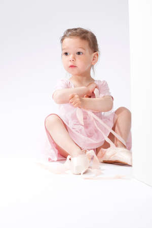 pointes: Portrait of Surprised Little Caucasian Ballerina Trying On Miniature Pointes. Posing Against White Background. Vertical Image Orientation