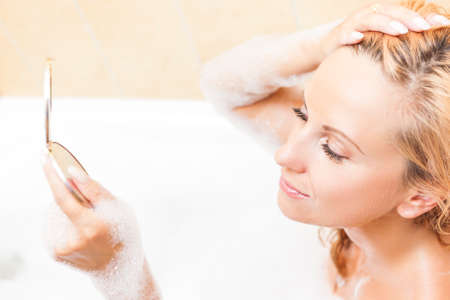 relaxion: Spa and Wellness Concepts and Ideas. Caucasian Blond Woman During Skin Makeup Process in Bathtub. Horizontal Image