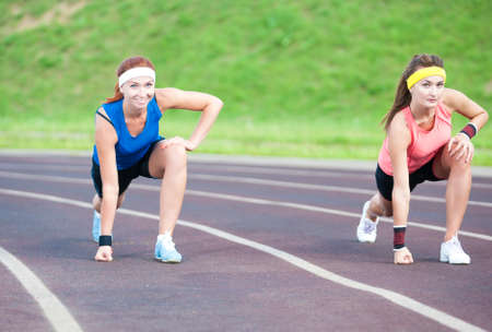prior: Two Caucasian Sportswomen Standing Prior to  Running On Sport Venue Outdoors. Horizontal Image Orientation Stock Photo