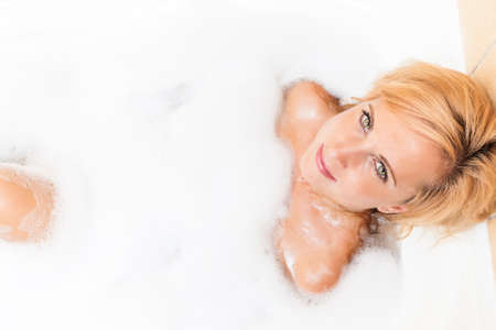 relaxion: Spa Concept and Ideas. Young Caucasian Blond Female having Relaxation Bathtub with Foam. Looking Upwards. Horizontal Image Composition Stock Photo