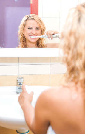 Caucasian Woman Brushing Her Teeth With Modern Electric Toothbrush in Bathroom. Vertical  Image