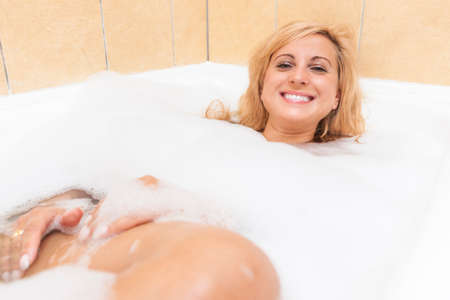 relaxion: Healthlife and Wellness Concepts and Ideas. Attractive Caucasian Female Enjoying Bath with Aromatic Foam.Horizontal Image