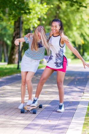 skate park: Two Happy Laughing Teenager Girls Skating Longboard Together in Park. Vertical Image Composition