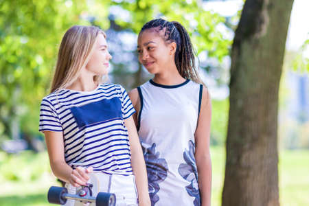 hair roller: Teenager Concepts. Two Teenage Girlfriends Together With Longboard Outdoors in Park.Horizontal Image