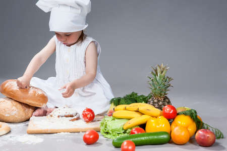 banana bread: Cute Funny Caucasian Female Cook with Lots of Vegetables In Front. Against Gray Background. Horizontal Composition Stock Photo