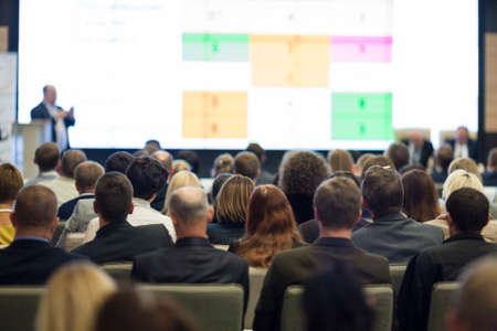 Business People Concept and Ideas. Large Group of People at the Conference Watching Presentation Charts on Screen in Front of Them. Horizontal Shot