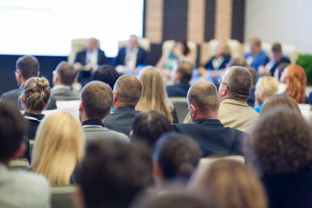 Group of Professionals At the Round table During the Conference. Speaking in Front of Large Group of People. Horizontal Image Composition