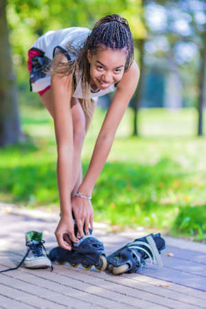 hair roller: Teenager Lifestyle Concepts. African American Teenage Girl Puts On Roller Skates in Park Outdoors.Vertical Image