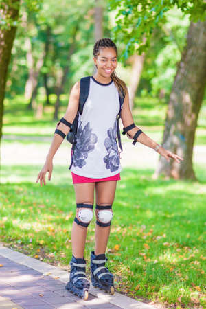 hair roller: Teenage Lifestyle Concepts and Ideas. Sportive African American Female Teenager Having Fun on Roller Skates in Park. Vertical Image Stock Photo