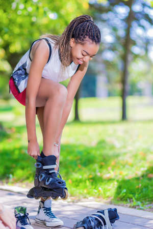 hair roller: Teenager Lifestyle Concepts. African American Teenage Girl Puts On Roller Skates in Park Outdoors.Vertical Image Composition