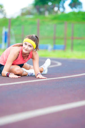 mujer deportista: Female Sport Concepts. Young Caucasian Sporstwoman Having Stretching Exercises On Stadium Outdoors. Vertical Composition Foto de archivo