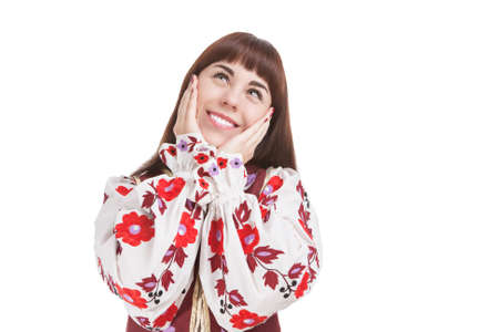 exclaiming: Natural Portrait of Caucasian Brunette Female Posing in National Flowery Dress. Showing Exclamation Touching Cheeks. Horizontal Image Orientation