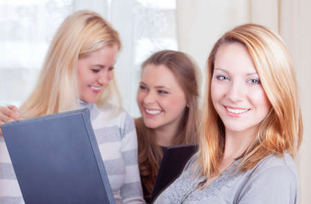 amusment: Youth Lifestyles Concepts. Three Caucasian Young Ladies With Laptop Posing Indoors.Horizontal Image Orientation