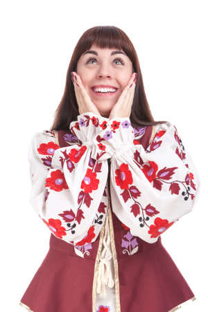 exclaiming: Natural Portrait of Caucasian Brunette Female Posing in National Flowery Dress. Showing Exclamation Touching Cheeks. Vertical Image Orientation