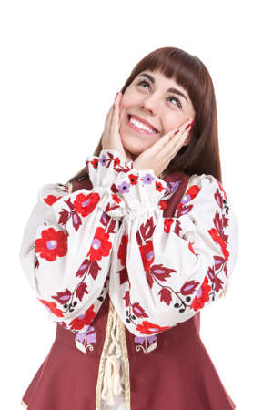 exclaiming: Natural Portrait of Caucasian Brunette Female Posing in National Flowery Dress. Showing Exclamation Touching Cheeks. Vertical Image