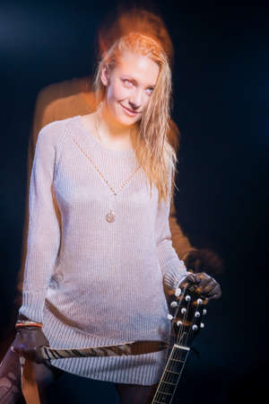 Portrait of Female Musician Posing with Guitar Against Black. Combination of Flash and Halogen Used. Vertical Image Orientation