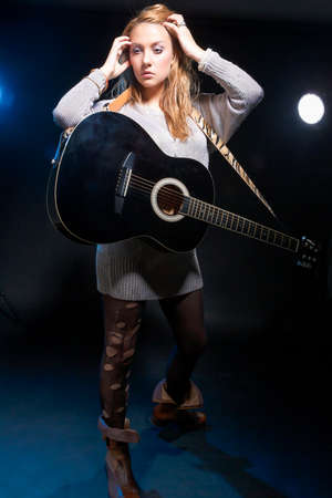 Musical Concepts and Ideas. Caucasian Blond Female Posing with Guitar Against Black. Vertical Image Orientation