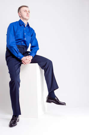 chinos: Young Adults Concepts. Full Length Portrait of Handsome Caucasian Man With Folded Hands Posing in Blue Shirt and Dark Blue Chinos Against White Background. Vertical Image Composition Stock Photo