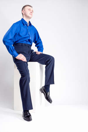 against white: Full Length Portrait of Handsome Caucasian Man Posing in Blue Shirt Against White Background. Looking Upwards. Vertical Image