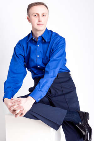 chinos: Young Adults Concepts. Portrait of Handsome Caucasian Man With Folded Hands Posing in Blue Shirt and Dark Blue Chinos Against White Background. Vertical Image Stock Photo