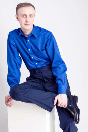 against white: Young Adults Concepts. Portrait of Handsome Caucasian Man Posing in Blue Shirt and Dark Blue Chinos Against White Background. Vertical Image Stock Photo