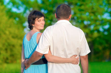 Family Values Concepts and Ideas. Two Caucasian Mature Adults Enjoying Together Outdoors. Walking Embraced in Park.Horizontal Image Orientation