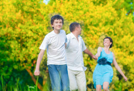 manos unidas: Familia caucásica de tres que se divierten junto y se ejecuta en bosque de verano con las manos juntas. tiro horizontal