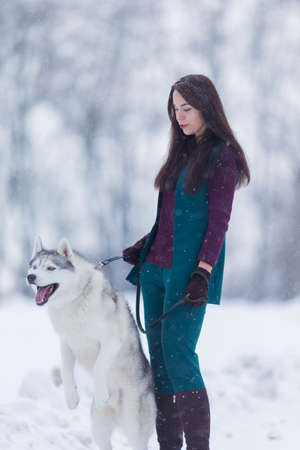 Caucasian Brunette Woman Keeping Her Husky Dog on a Short Leash During a Stroll in Winter Time Outside.Vertical Image Stock Photo