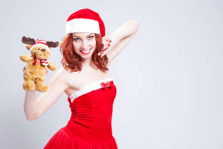 Portrait of Caucasian Santa Helper with Christmas Present in Hands. Over White Background. Horizontal Image