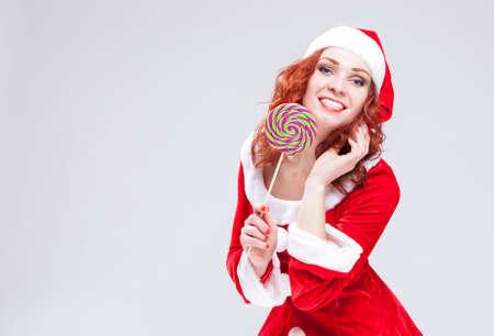 Portrait of Happy Smiling Santa Helper with Lollipop. Against white. Horizontal Image Composition