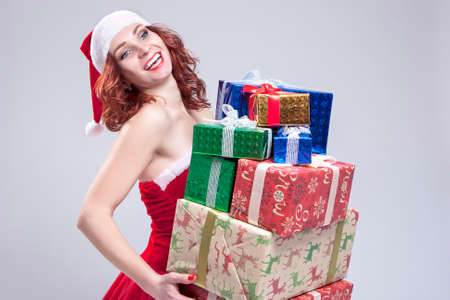 Christmas and New Year Concept and Ideas. Positive Caucasian Snow Maiden Holding a Big Stack of Gift Boxes on Hands and Smiling. Posing on White. Horizontal Image Orientation Stock Photo