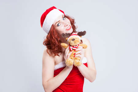 Portrait of Caucasian Santa Helper with Christmas Present in Hands. Over White Background. Horizontal Image Orientation Stock Photo